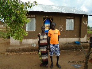 Figure  SEQ Figure \* ARABIC 2 Joyce and her son pause in front of their shelter constructed by PWJ