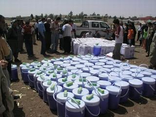 避難民キャンプで配給される保冷水筒などの物資