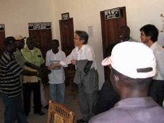 修復された職員室で握手を学校関係者と握手を交わす