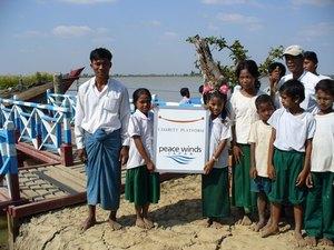 完成した船着場で子どもたちと並ぶタン・ズィン村長(左)