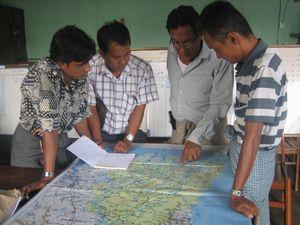 配給目的地を確認するPWJミャンマー人スタッフ、ニー・トウェー(左から2番目)と船会社の人