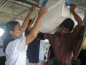 ファミリーキットを村人に渡すPWJスタッフのナインナイン・アウン(左端)