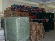 倉庫に積み上げられた配布予定の毛布やバケツ、洗剤など