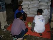 ディリの脱穀工場でコーヒー水分値を測る組合代表とPWJスタッフ