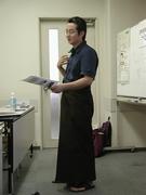 民族衣装ロンジーを着て報告するPWJ明城
