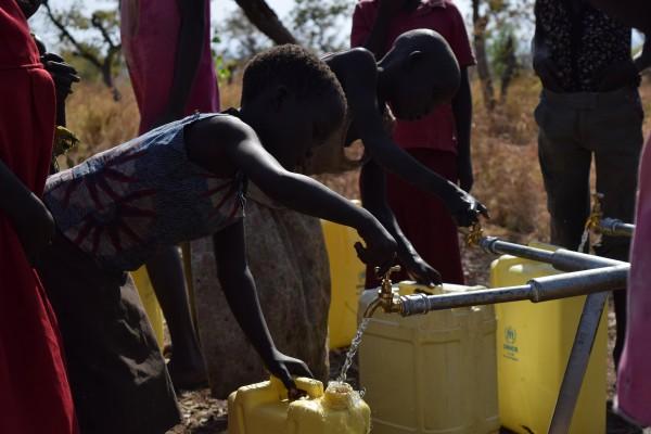 メイン写真)PWJが設置したばかりの水タンクから水をくむ子どもたち
