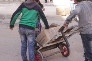 食糧キットを運ぶのを手伝う子どもたち