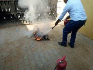 消火器を使って火を消す方法を模擬演習するインストラクター