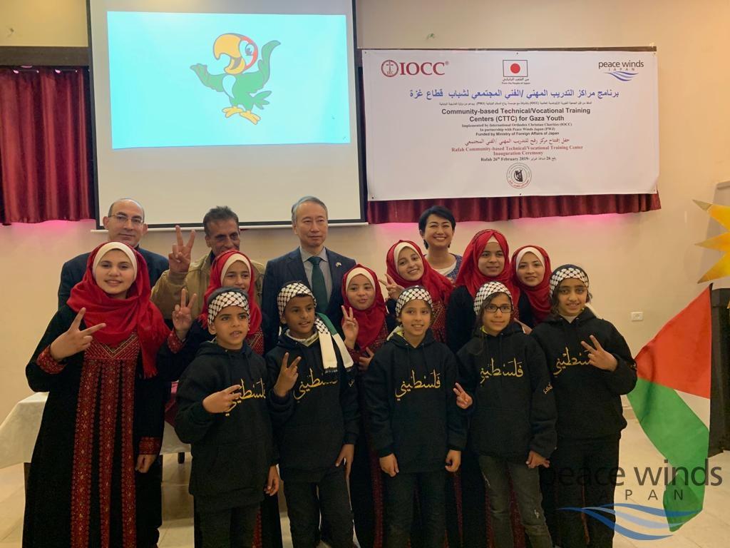 センター開所式で手話の歌を披露してくれた地元のろう学校の子供たちとIOCCエルサレム所長マルキ氏、ラファハの提携団体El Amal Rehabilitation Centerのアル・アバド会長、大久保パレスチナ関係担当大使とピースウィンズの平井(後列、左から右)
