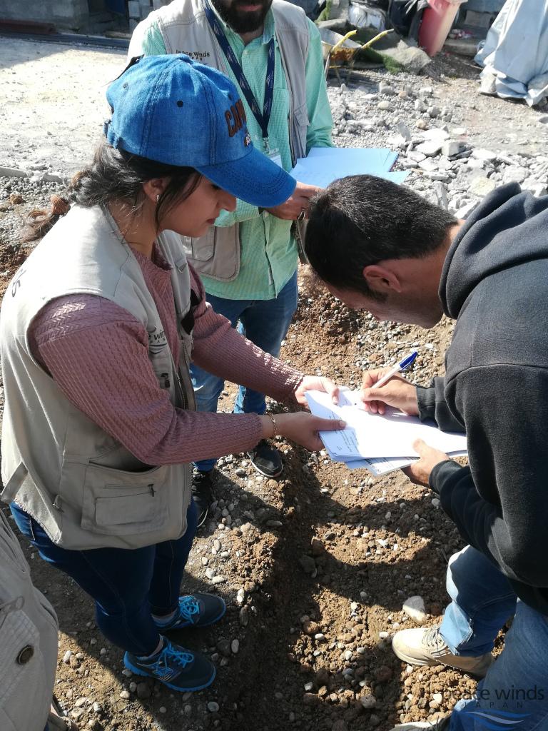 ピースウィンズの現地スタッフから賃金を受け取る作業員(右)。キャンプに住む難民を雇って所得創出の機会を作っている。