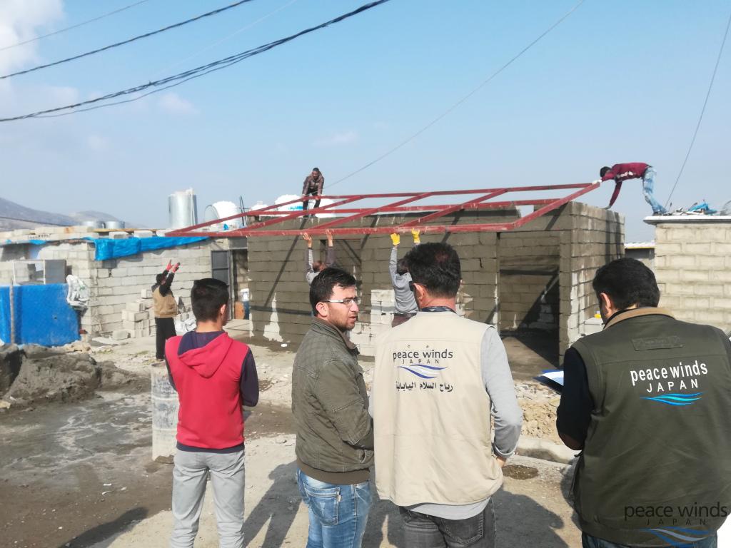 テントを取り除き、コンクリートブロックで家の壁が完成した後、 屋根のフレーム部分を設置中。